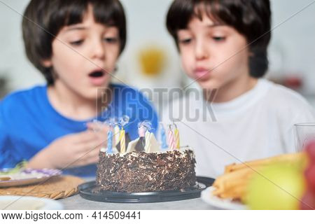 Birthday Boys. Two Little Latin Boys Blowing Candles On A Birthday Cake While Celebrating Birthday T