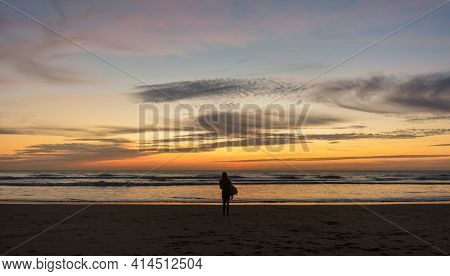 Surfing Sunset. Silhouette Of Female Surfer Carrying Boards Along The Sand Of A Beach