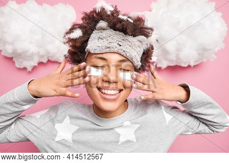 Horizontal Shot Of Pleased Afro American Woman Applies Beauty Patches Under Eyes To Reduce Puffiness
