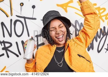 Urban Lifestyle Adolescent And Youth Culture Concept. Joyful Female Teenager Dances Against Graffiti