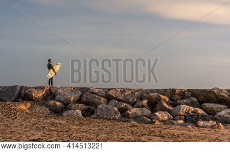 Man Surfer Carrying His Surfboard At Sunrise - Hipster Male In Wetsuit Waiting For The High Waves On