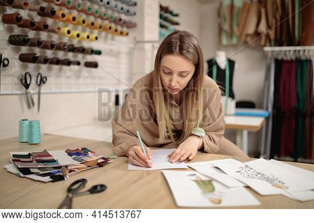 Woman Fashion Designer Draws Sketches. Attractive Young Female Dressmaker Sketching In Studio