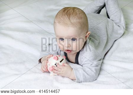 Pink Piggy Bank. Defocused Baby At Home.copy Space-concept Of Financial Planning, Personal Savings,