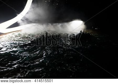 Silhouettes Of A Crowd Standing At Blurred Military War Ship On Foggy Background. Selective Focus. P