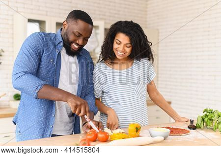 Young Happy Family Prepares Their First Dish Together In A New Apartment, Husband Cuts Cheese For Pi