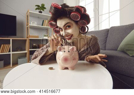 Smiling Young Woman With Face Mask And Hair Curlers Putting Coins In Her Piggy Bank