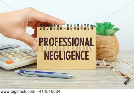 Professional Negligence Is Written On A Notepad On An Office Desk With Office Accessories.