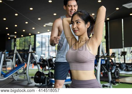 The Personal Trainer Helps Asian Women With Arm Triceps Workout In Fitness Gym. Concepts Of Exercise