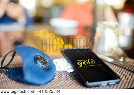 Blue Cloth Mask With Mobile Phone At Side With A Zomato Gold Logo In Restaurant Showing The Populari