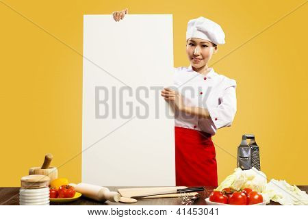 Asian female chef holding poster for the text