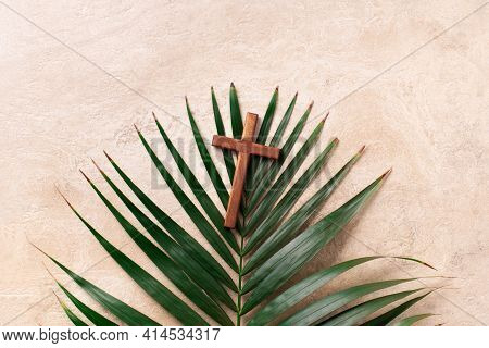 Palm Sunday Concept. Wooden Cross Over Palm Leaves. Reminder Of Jesus Sacrifice And Christ Resurrect