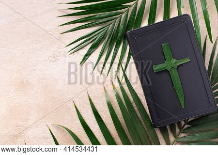 Palm Sunday Concept. Palm Cross On Open Holy Bible And Palm Leaves. Reminder Of Jesus Sacrifice And