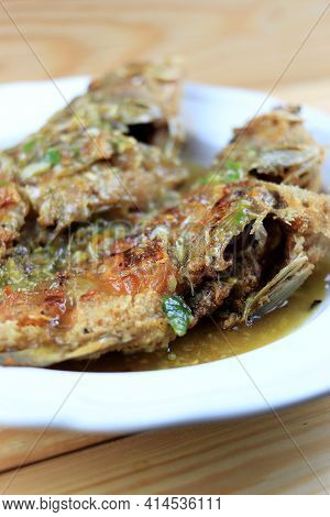 Thai Giant Gourami Fish And Garlics Deep Fried And Sweet Spicy Sauce In White Dish On Pine Wooden Ta