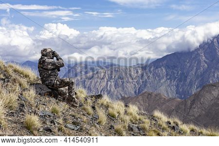 Man In Camouflage On The Slope Is Watching Through Binoculars In The Mountains. Hunter Looks Through