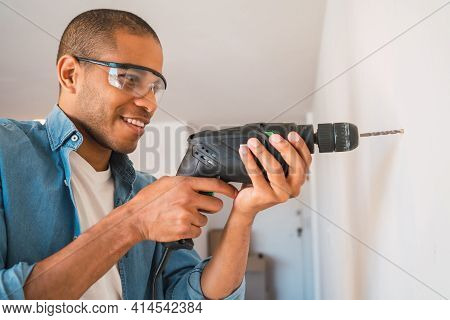 Young Man With A Electric Drill And