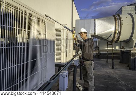 Hvac Technician Servicing Commercial Air Conditioning Equipment On Building Roof Top