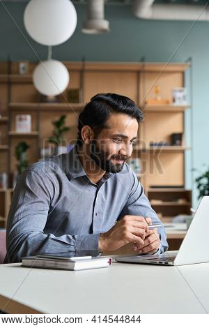 Smiling Bearded Indian Businessman Working On Laptop At Home Office. Young Indian Student Using Comp
