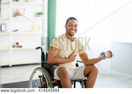 Physical Rehabilitation For Disabled People. Handicapped Black Guy In Wheelchair Making Exerises Wit