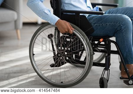 Cropped View Of Disabled Black Man Sitting In Wheelchair At Home. Impairment And Mobility Aids Conce