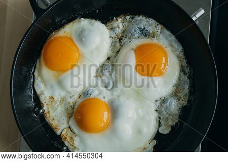 Keto Meal Eggs Frying On Hot Cast Iron Frying Pan, Three Fried Yellow Yolk, Ketogenic Diet