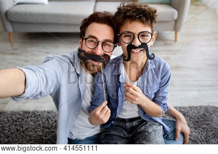 Funny Selfie. Happy Father And Son Taking Selfie, Holding Fake Moustache On Sticks And Smiling At Ca