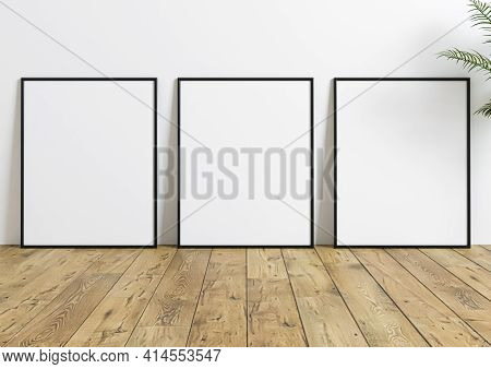 Triple Black Frame Mockup On Wooden Floor With Green Plant And White Wall Behind It. Empty Poster Th