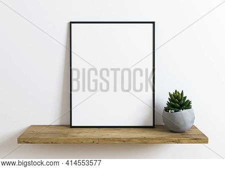 Black Frame Mockup On Wooden Shelf With Green Small Plant In A Vase And White Wall Behind It. Empty