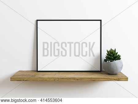 Black Frame Horizontal Mockup On Wooden Shelf With Small Green Plant In A Vase And White Wall Behind