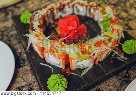 Maki Sushi Rolls With Salmon On Black Stone On Dark Background. With Ginger And Wasabi. Sushi Menu.