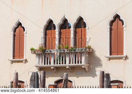 Facade Of Venetian House With Typical Old Venetian Windows With Closed Shutters On It. Sunny Day. Ve