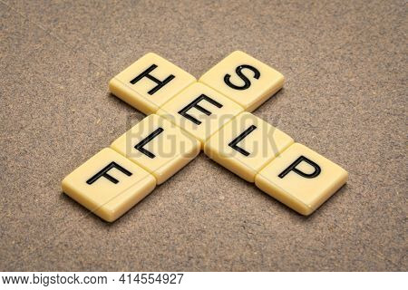 self help crossword in ivory letter tiles against textured handmade paper, personal development and self care concept