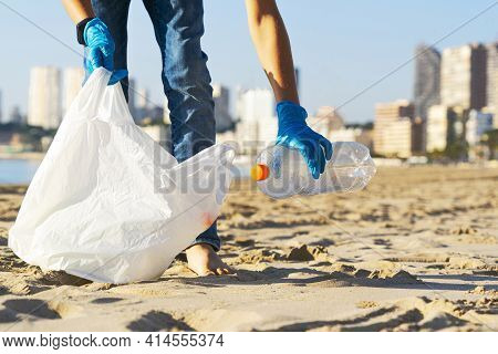 Cleaning Beach From Plastic. Hand Picking Up Plastic Bottle Trash From The Beach And Putting Into Pl