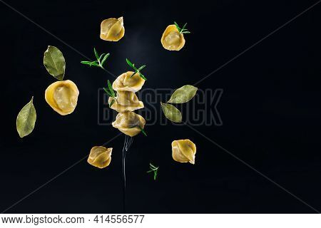 Food Levitation.dumplings With Meat Fly Into The Plate On A Black Background.