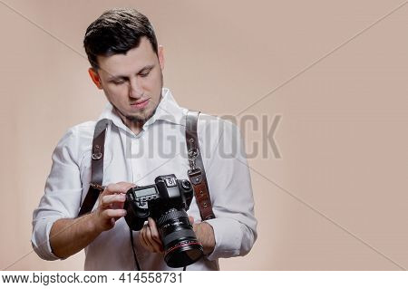 Photographer With Camera On Brown Background, Successful Professional Male Looks At Photos On Screen