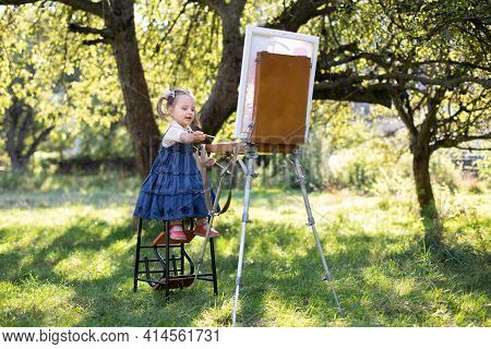 Painting On Canvas Using Easel In The Green Summer Garden With Bright Sunlight. Caucasian Little Art