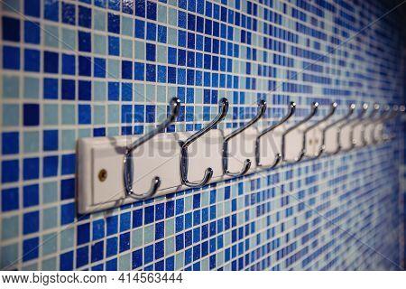 Metal Hanger Hooks On Blue Tiled Wall