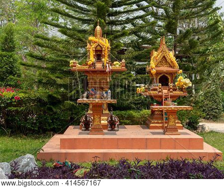 Altar With Offerings To Budha In Thailand, Viewed From The Front, With Plants In The Foreground And