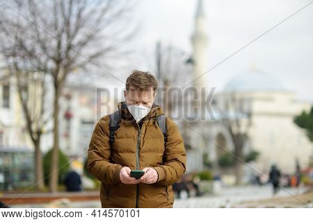 Mature Man Wearing Face Mask Using Phone On Street Of Istanbul, Turkey. Historical Center Of The Cit