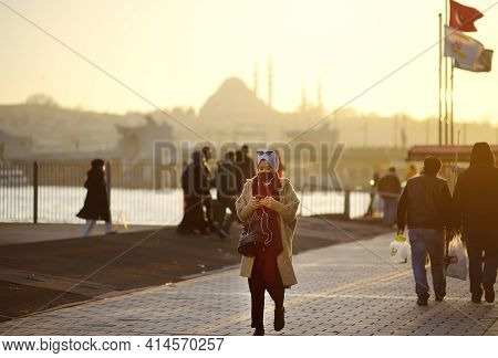 Istanbul, Turkey - March 4, 2021: People Walking Of Embankment Of Golden Horn On Background Of Famou