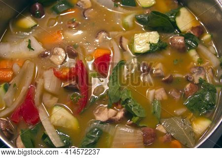 Close-up Of A Pot Of Hearty Homemade Vegetable Soup With Broth, Mushrooms, Carrots, Spinach, Zucchin