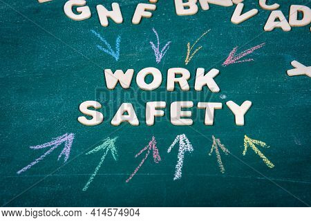 Work Safety. White Letters Of The Wooden Alphabet. Colored Pieces Of Chalk On A Green Chalk Board