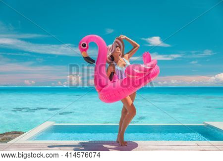 Summer suntan woman wearing hat and sunglasses for sun protection while sunbathing on Caribbean beach vacation by luxury infinity swimming pool. Fun flamingo pool toy air float.