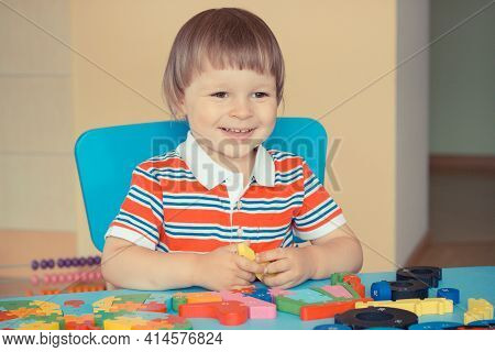Happy Smiling Preschooler Playing With Puzzle. Child Development Concept