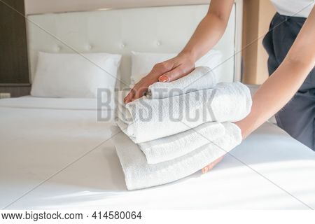 Cropped Shot Of Hotel Maid Arranging The Stack Of Towels On Bed. Conceptual Of Female Chambermaid Ma