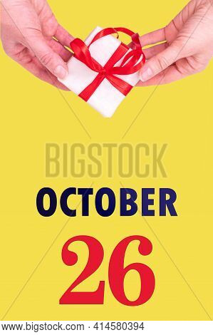 October 26th. Festive Vertical Calendar With Hands Holding White Gift Box With Red Ribbon And Calend