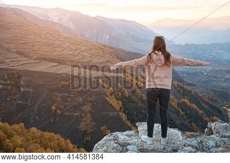 Young Woman With Loose Flowing Hair Stands On Grey Rocky Hilltop Looking At Bright Sun Rising From B
