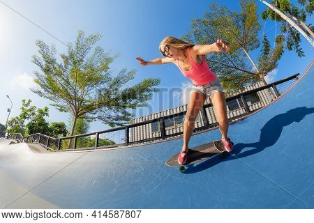 Skateboarder In Action. Young Woman Making Trick On Surf Skate Longboard In Outdoor Skatepark Bowl.