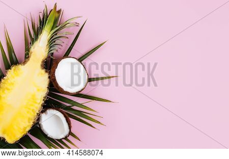 Flat Lay With Cut Halves Of Fresh Pineapple, Coconut And Green Palm Leaf On A Pastel Pink Background