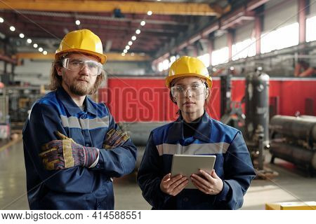 Two young serious engineers in protective workwear looking at you while standing in front of camera, female worker using digital tablet