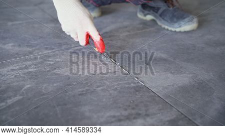 The Process Of Laying Tiles On The Floor. The Process Of Removing Grout Between Floor Tiles. Ceramic